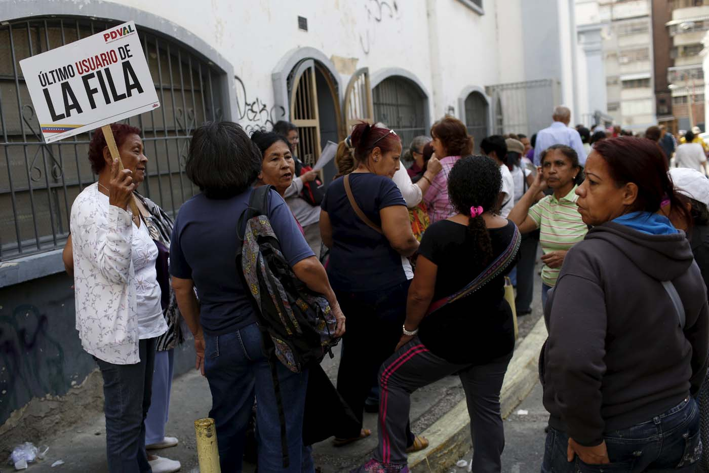 """A elder woman holds a placard that reads, """"The last user of the line"""", while she waits next to others in a line for the elderly outside a PDVAL, a state-run supermarket, to buy chicken in Caracas January 22, 2016.  Venezuela's opposition refused on Friday to approve President Nicolas Maduro's """"economic emergency"""" decree in Congress, saying it offered no solutions for the OPEC nation's increasingly disastrous recession. Underlining the grave situation in Venezuela, where a plunge in oil prices has compounded dysfunctional policies, the International Monetary Fund on Friday forecast an 8 percent drop in gross domestic product and 720 percent inflation this year. REUTERS/Carlos Garcia Rawlins"""