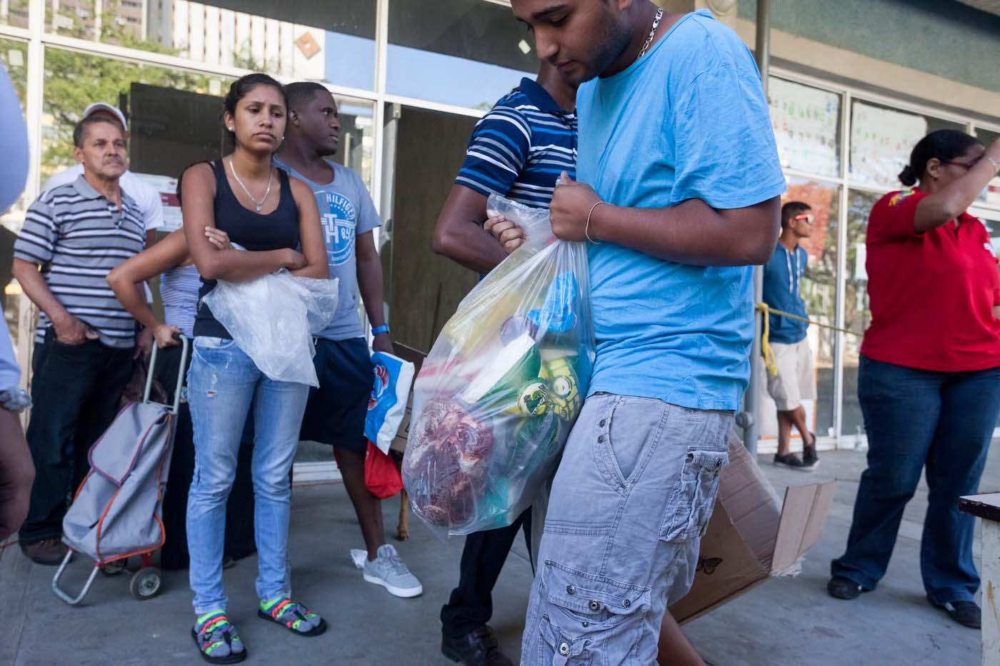 """CAR01. CARACAS (VENEZUELA), 23/01/2016.- Un hombre carga una bolsa con alimentos hoy, sábado 23 de enero de 2016, en la ciudad de Caracas (Venezuela). El presidente del Parlamento venezolano, el opositor Henry Ramos Allup, reiteró hoy que los problemas que afronta su país con una aguda crisis económica de carestía y escasez se agravarán si Nicolás Maduro sigue en la jefatura del Estado. La situación económica del quinto productor de petróleo del mundo se ha visto golpeada por la caída de los precios del crudo, que inició en septiembre de 2014 cuando se cotizaba en 90 dólares por barril y que cerró esta semana en 21,63 dólares. """"Este Gobierno va a resolver nada; mientras esté allí todos los problemas de Venezuela van a empeorar totalmente. Hasta que no salgamos democráticamente de este Gobierno, Venezuela no se va a recuperar ni podrá resolver ninguno de sus problemas"""", subrayó en un discurso ante manifestantes antigubernamentales en Caracas. EFE/MIGUEL GUTIERREZ"""