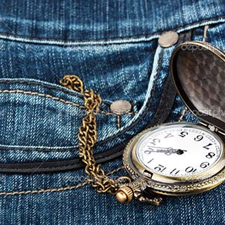Closeup pocket watch in pocket of jeans