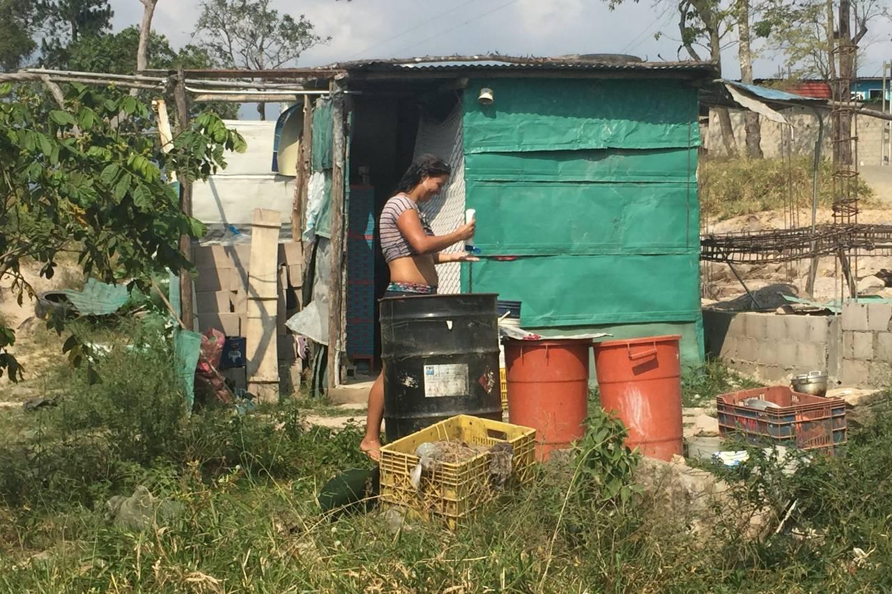 Una mujer se baña con agua guardada en contenedores fuera de su casa en San Josecito, lo cual puede servir de incubadora a los mosquitos que transmiten el zika. PHOTO: SARA SCHAEFER MUÑOZ/THE WALL STREET JOURNAL