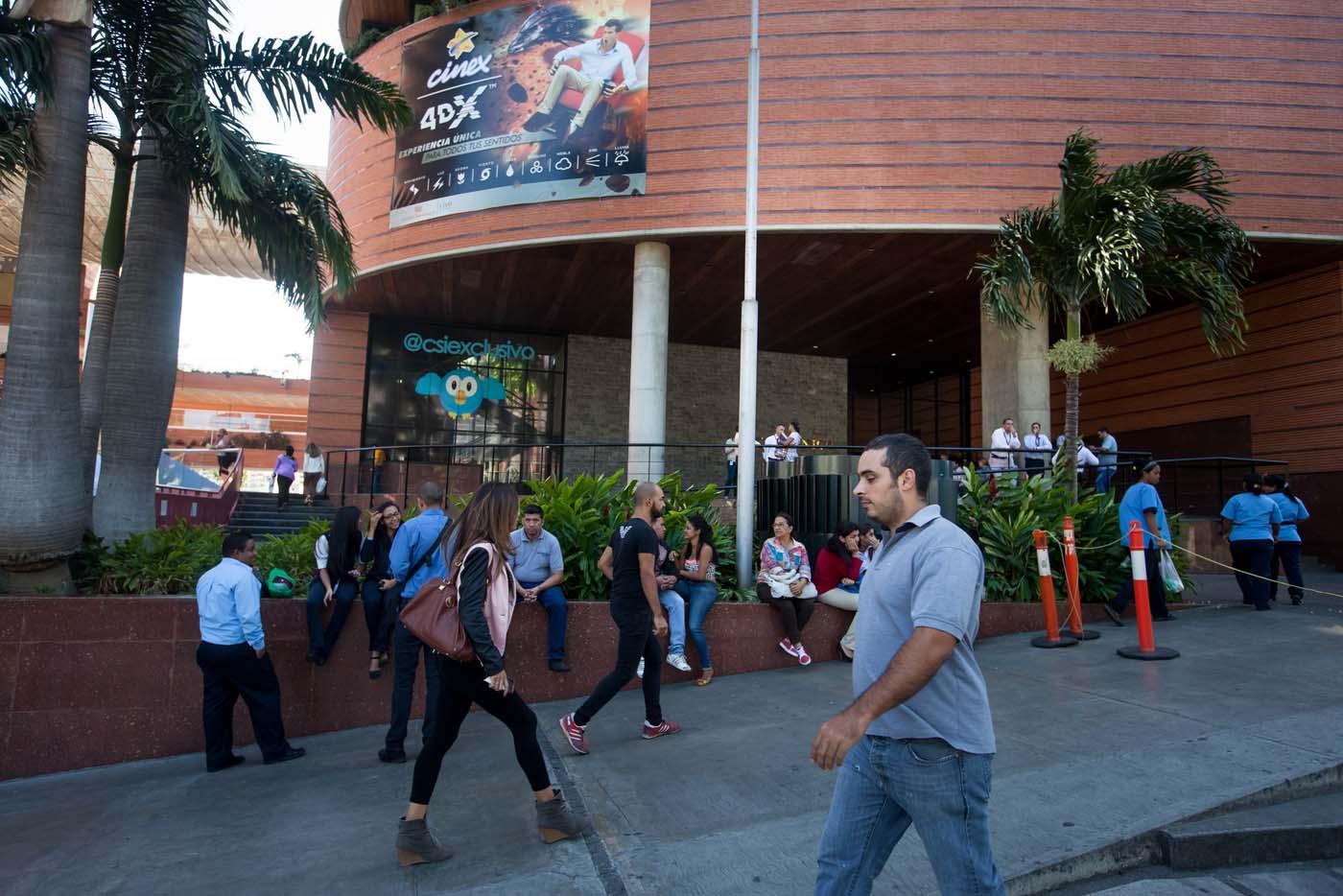 CAR01. CARACAS (VENEZUELA), 10/02/2016.- Varias personas esperan afuera de un centro comercial hoy, miércoles 10 de febrero de 2016, en Caracas (Venezuela). Los centros comerciales de Venezuela iniciaron hoy sus actividades con un horario restringido que los lleva a trabajar durante un promedio de cuatro horas diarias, una situación que elevó las alarmas de las organizaciones relacionadas con el sector que auguran pérdidas de dinero y empleos. EFE/Miguel Gutiérrez