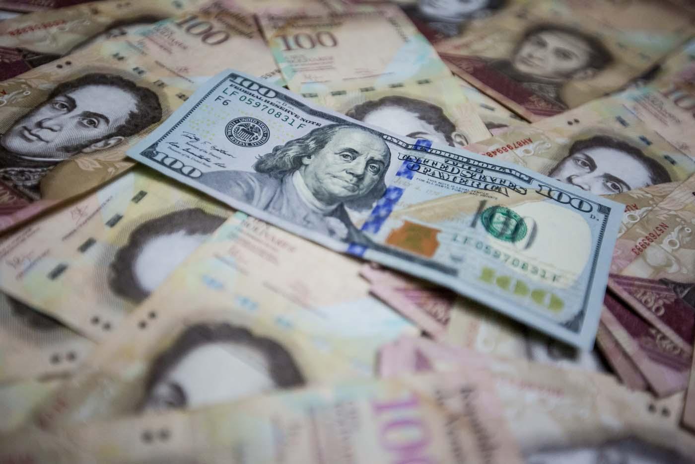 CAR04. CARACAS (VENEZUELA), 17/02/2016.- Fotografía de billetes de pesos mexicanos y dólares estadounidenses hoy, miércoles 17 de febrero de 2016, en Caracas (Venezuela). El presidente venezolano, Nicolás Maduro, anunció hoy una serie de medidas económicas que incluye el primer aumento del precio de la gasolina en el país en 27 años, que sube más de un 6.000 %, una devaluación del bolívar del 58,7 % y un aumento del 20 % de los salarios básicos. EFE/Miguel Gutiérrez