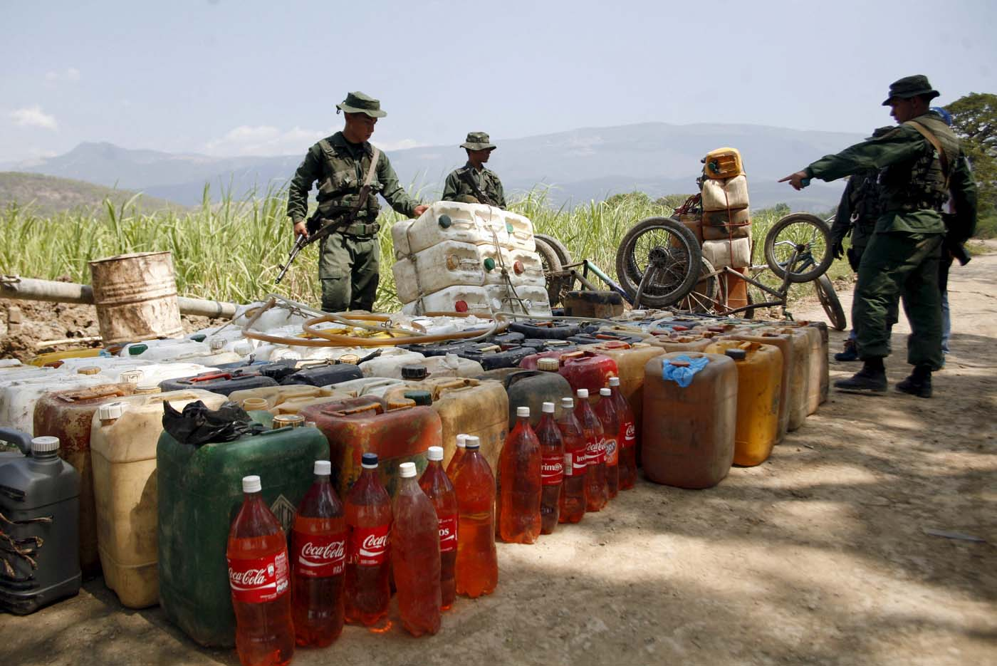 Venezuelan soldiers collect containers with gasoline abandoned by smugglers near the Colombian border in San Antonio, in the state of Tachira, February 17, 2016. REUTERS/Carlos Eduardo Ramirez. EDITORIAL USE ONLY. NO RESALES. NO ARCHIVE.