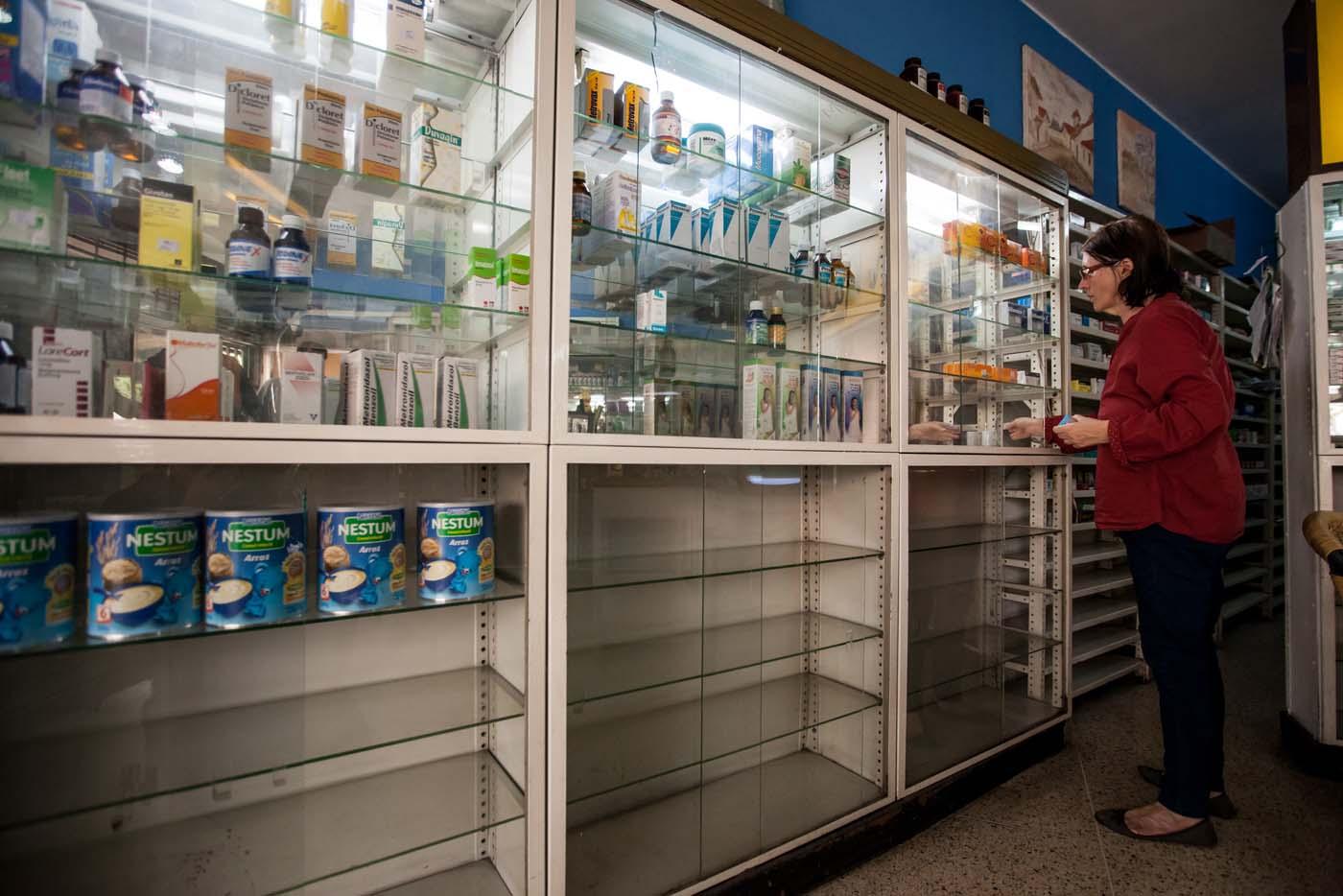 """ACOMPAÑA CRÓNICA: VENEZUELA SALUD CAR38. CARACAS (VENEZUELA), 14/04/2016.- Beatriz Gorostiza, una de las encargadas de la farmacia """"San Vicente"""", busca medicamentos en un estante este, jueves 14 de abril del 2016, en la ciudad de Caracas (Venezuela). La escasez de medicamentos en Venezuela sigue siendo una tragedia visible en farmacias y hospitales, semanas después de que el Parlamento declarara una """"crisis humanitaria de salud"""" que, entre otros cosas, se estaría manifestando en la falta de disponibilidad de 872 fármacos esenciales. EFE/MIGUEL GUTIÉRREZ"""