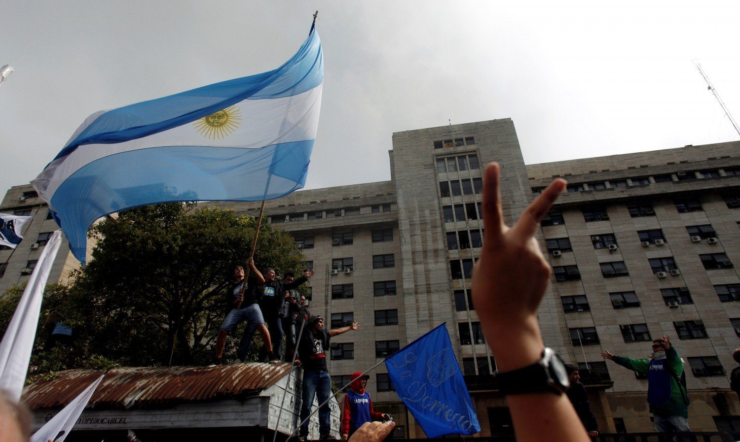 Supporters of former Argentine President Cristina Fernandez de Kirchner wave an Argentine national flag outside a Justice building where she attended court to answer questions over a probe into the sale of U.S. dollar futures contracts at below-market rates by the central bank during her administration, in Buenos Aires, Argentina, April 13, 2016. REUTERS/Martin Acosta