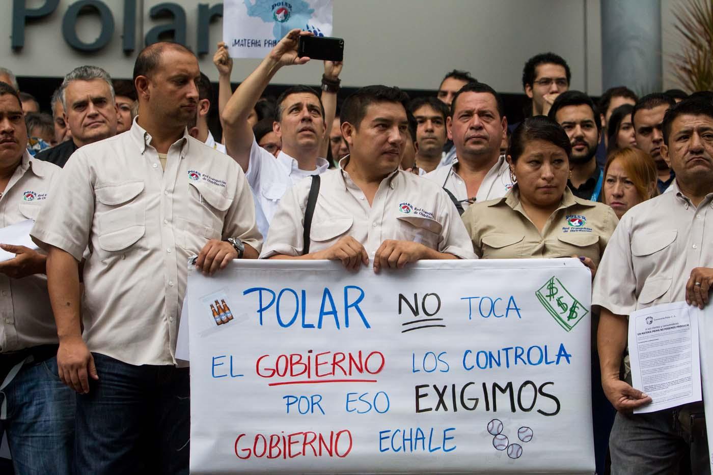 CAR23. CARACAS (VENEZUELA) 22/04/2016.- Trabajadores de empresas Polar participan en una manifestación en las inmediaciones de su edificio hoy, viernes 22 de abril del 2016, en la ciudad de Caracas (Venezuela). Los trabajadores del consorcio Polar, la principal compañía de alimentos de Venezuela, demandaron hoy al Gobierno que liquide divisas para honrar los compromisos con proveedores e importar materiales para poder continuar con sus operaciones en el país. EFE/MIGUEL GUTIÉRREZ