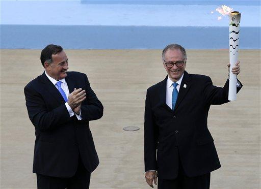 El presidente del comité organizador de los Juegos Olímpicos de Río de Janeiro, Carlo Nuzman, derecha, sostiene la antorcha olímpica tras recibirla de manos del líder del comité olímpico de Grecia, Spyros Capralos, el 27 de abril de 2016, en Atenas. (AP Photo/Thanassis Stavrakis)