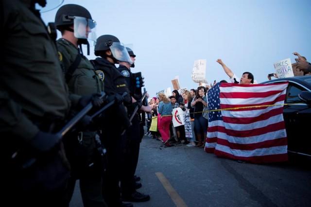 Policías antidisturbios marcan una distancia de seguridad entre simpatizantes y opositores (d) del candidato republicano Donald Trump durante un acto de campaña de en Costa Mesa, California (EEUU). EFE