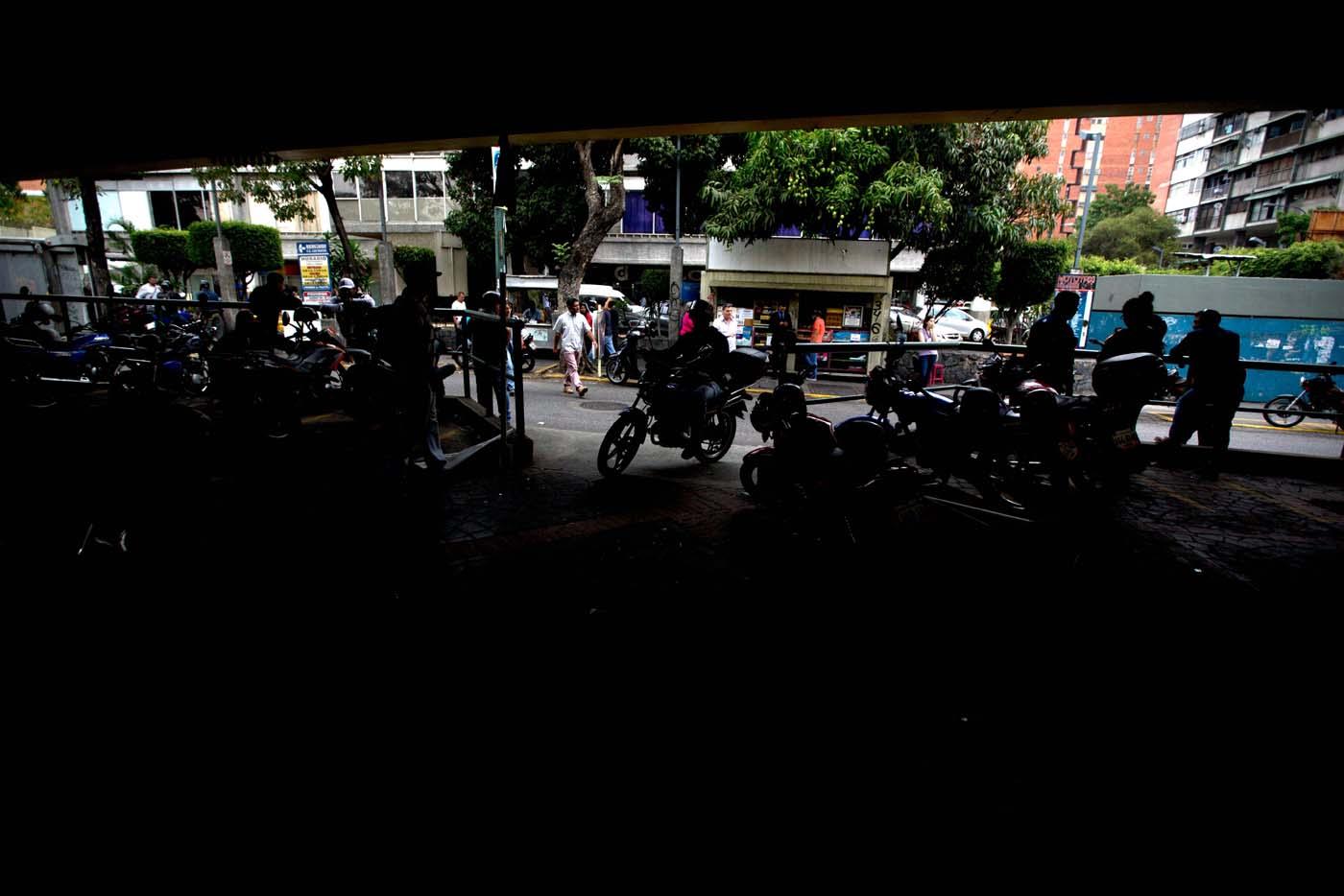 En esta imagen del 7 de abril de 2016, conductores de moto-taxis esperan a clientes en su estación cerca del lugar en el que Roberto Bernal fue golpeado y quemado vivo luego de que se le acusara de robar el equivalente a 5 dólares en Caracas, Venezuela. Los linchamientos en contra de las personas acusadas de robos, se ha vuelto algo común en esta nación de 30 millones de habitantes y azotada por la delincuencia, y que alguna vez fuera una de las más ricas y seguras de Latinoamérica. (Foto AP/Fernando Llano)