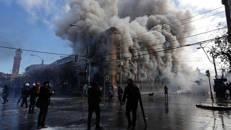 La presidente Michelle Bachelet rindió cuentas ante el Congreso de lo realizado en poco más de dos años de gestión, mientras en el centro de Valparaíso, sede del legislativo, se producían graves disturbios con incendio de varios edificios, que dejaron como saldo un muerto / Foto cortesía: Infobae