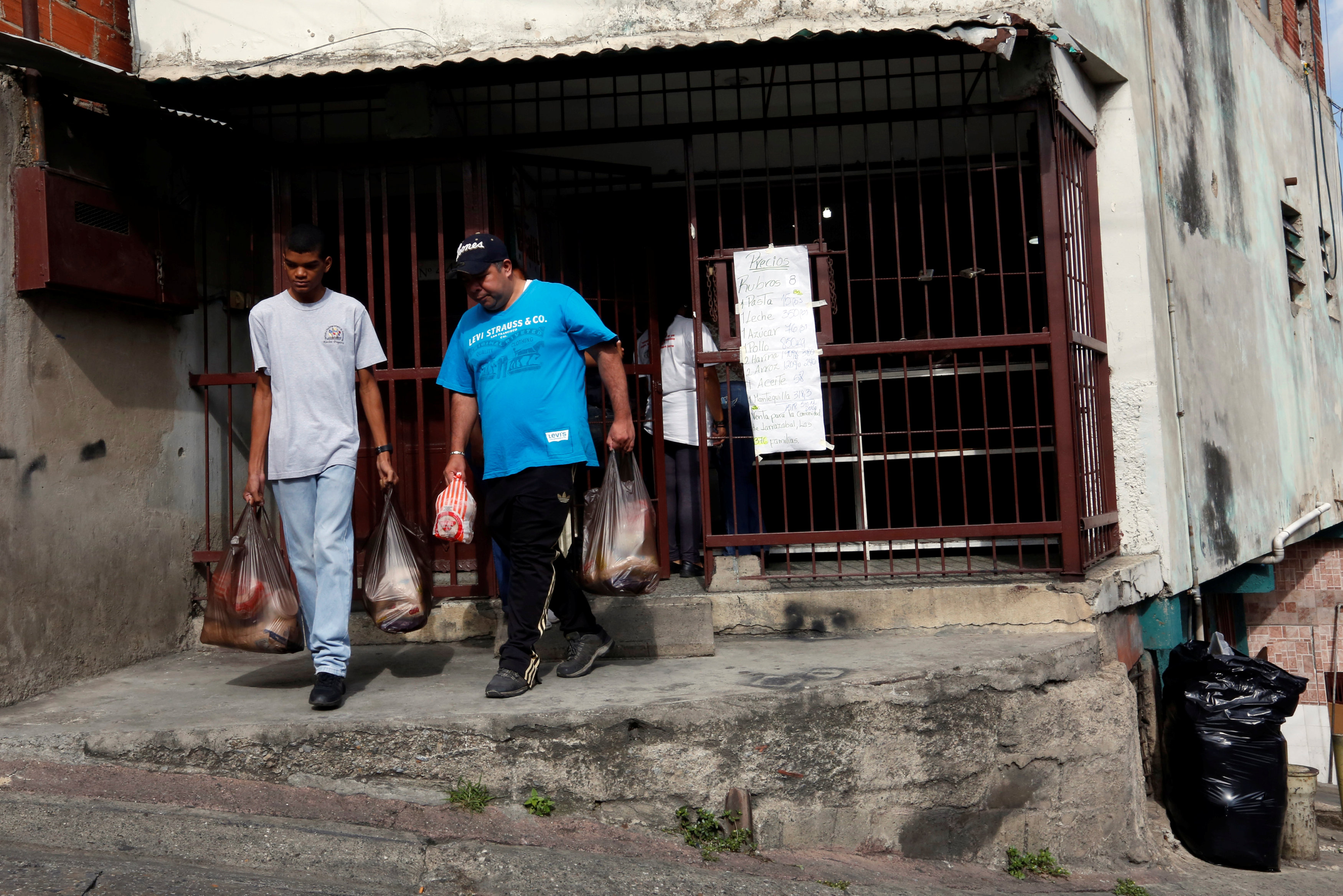 Residentes salen de un centro comunitario con bolsas de alimentos que compraron a bajo precio REUTERS/Carlos Jasso