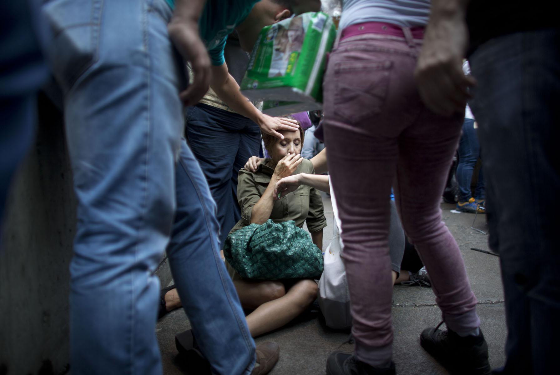 En esta fotografía del 5 de mayo de 2016, Irama Carrero recibe asistencia de otras personas después de desmayarse mientras estaba formada en una fila afuera de una tienda de Caracas, Venezuela. Carrero, quien dijo que no había comido ese día, pasó horas formada en la fila para ancianos cuando se desmayó. Nadie detuvo su caída y su cabeza pegó en el piso de concreto. Cuando recuperó la conciencia, comenzó a vomitar. (AP Foto/Ariana Cubillos)