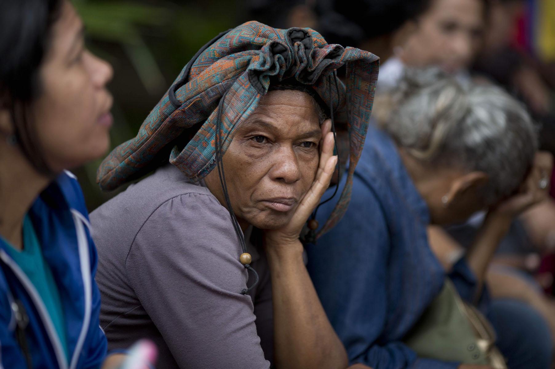 En esta fotografía del martes 3 de mayo de 2016, Adelaida Ospina se cubre la cabeza con un bolso de mano mientras espera en la fila afuera de un supermercado de Caracas, Venezuela, con el fin de comprar alimentos. El venezolano promedio pasa 35 horas al mes esperando para comprar productos básicos. Ospina dijo que llegó a las 5:40 de la mañana. (AP Foto/Ariana Cubillos)