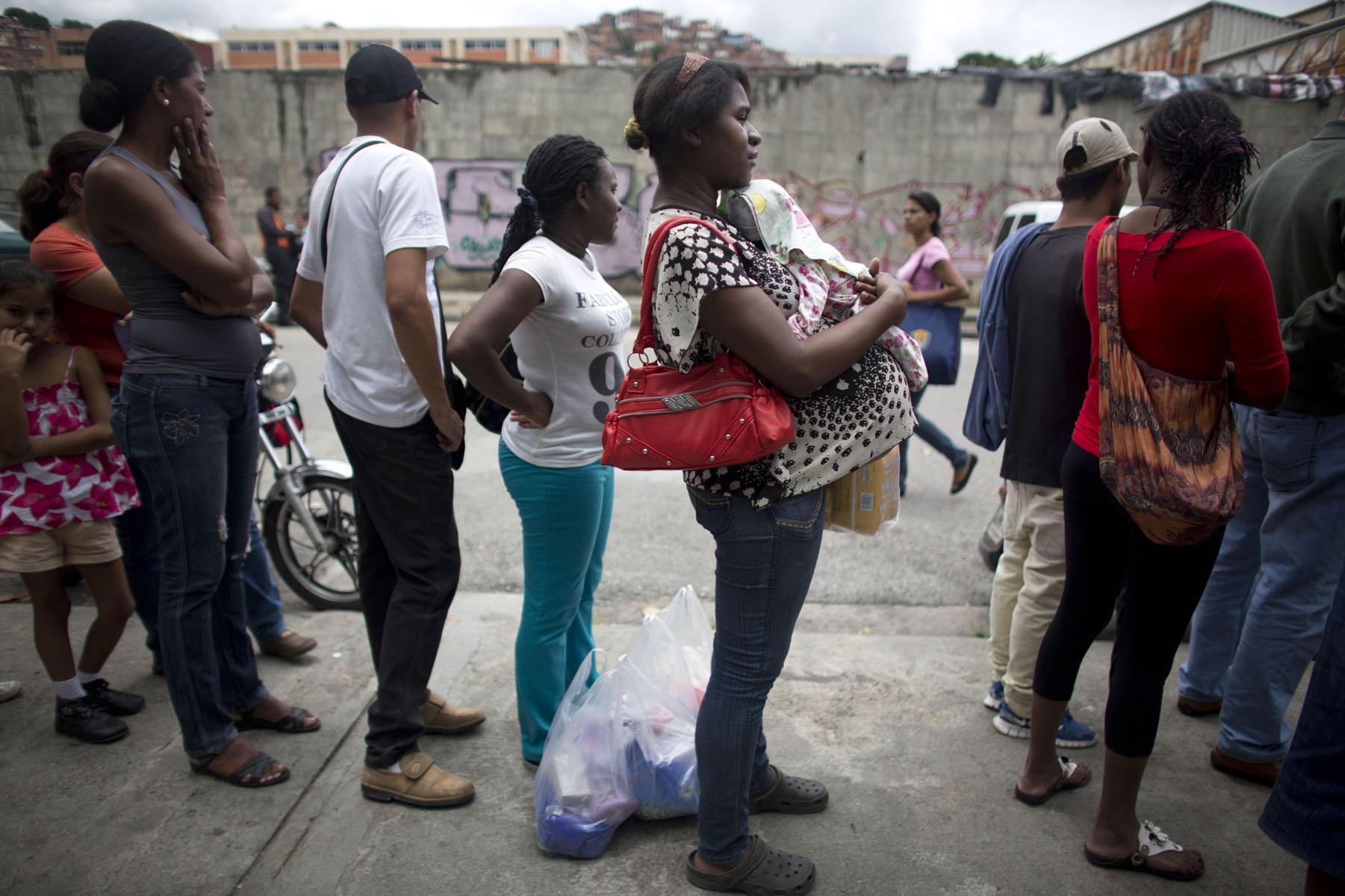 En esta fotografía del lunes 2 de mayo de 2016, una mujer embarazada espera en la fila afuera de un supermercado de Caracas, Venezuela, para comprar comida. En algunas tiendas, las embarazadas y los ancianos usan filas preferentes, pero no en esta tienda. (AP Foto/Ariana Cubillos)