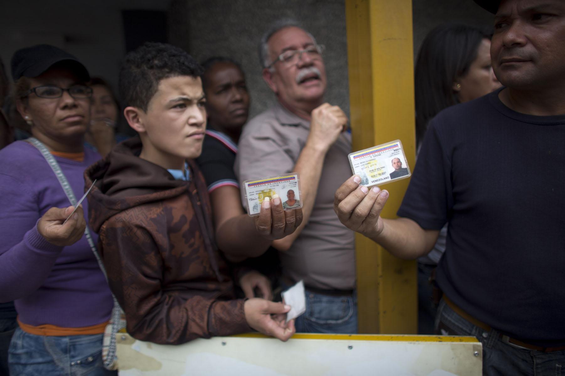 En esta fotografía del martes 3 de mayo de 2016, algunas personas muestran sus carnés de identidad mientras esperan formados afuera de un supermercado de Caracas, Venezuela, para comprar alimentos. A todos los venezolanos, incluidos los menores de edad, se les asignan dos días a la semana para hacer compras en función de sus números de identidad. Algunos usan carnés de identidad falsos para tener más días de compra. (AP Foto/Ariana Cubillos)