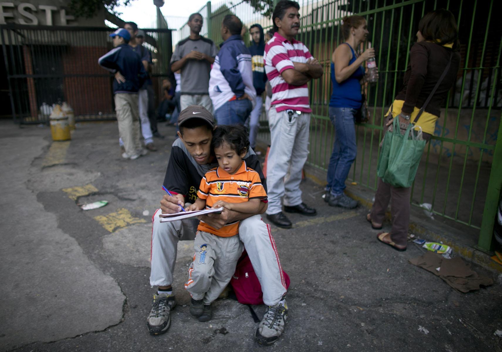 En esta imagen, tomada el 4 de julio de 2016, Eder Noriega, de 25 años, enseña los números a su hijo Santiago, de 3, mientras esperan en una fila para comprar comida en un supermercado en Caracas, Venezuela. A medida que las filas se vuelven más largas, se han convertido en un escenario de la vida cotidiana. (AP Foto/Ariana Cubillos)