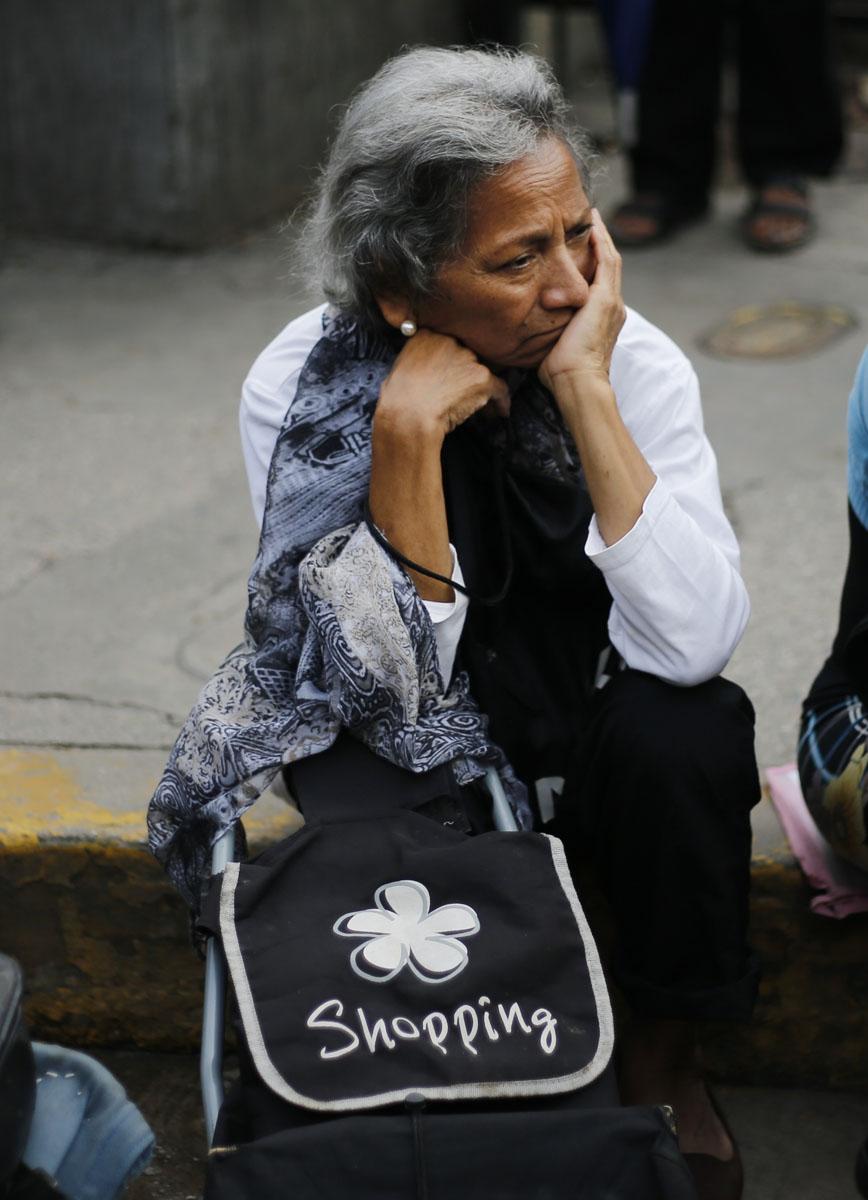 En esta imagen, tomada el 8 de julio de 2016, una mujer espera en una fila en el exterior de un supermercado para comprar comida, en Caracas, Venezuela. Las carencias ocupan el primer lugar entre las inquietudes de los votantes, por encima de la seguridad. Lo cual es insólito en un país con una de las tasas de homicidios más altas del mundo. (AP Foto/Ariana Cubillos)