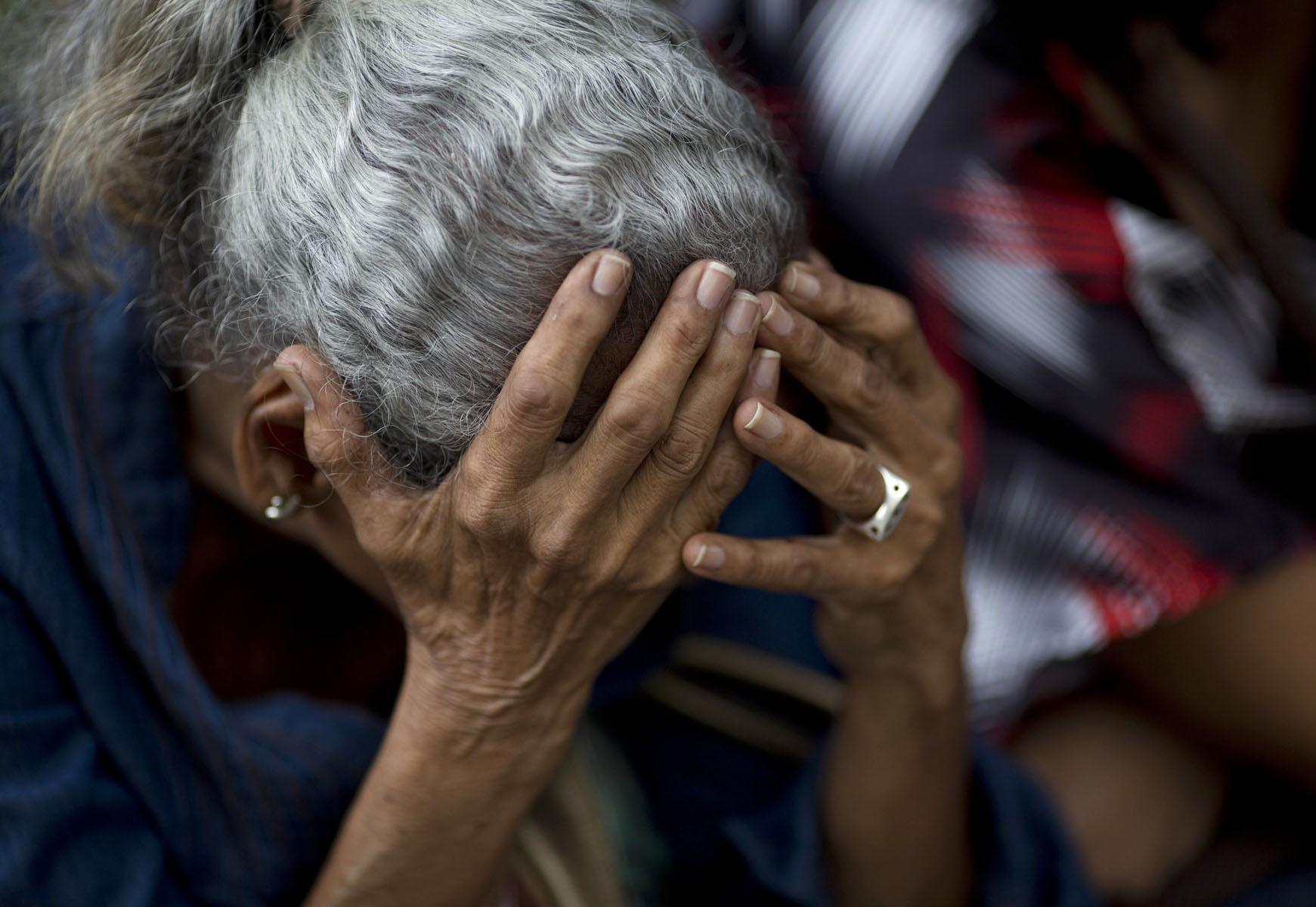 En esta imagen, tomada el 3 de mayo de 2016, una mujer se sostiene la cabeza entre las manos mientras espera en una fila en el exterior de un supermercado para comprar comida, en Caracas, Venezuela. Nueve de cada 10 personas dicen que no pueden comprar alimentos suficientes, de acuerdo con un estudio de la Universidad Simón Bolívar. (AP Foto/Ariana Cubillos)