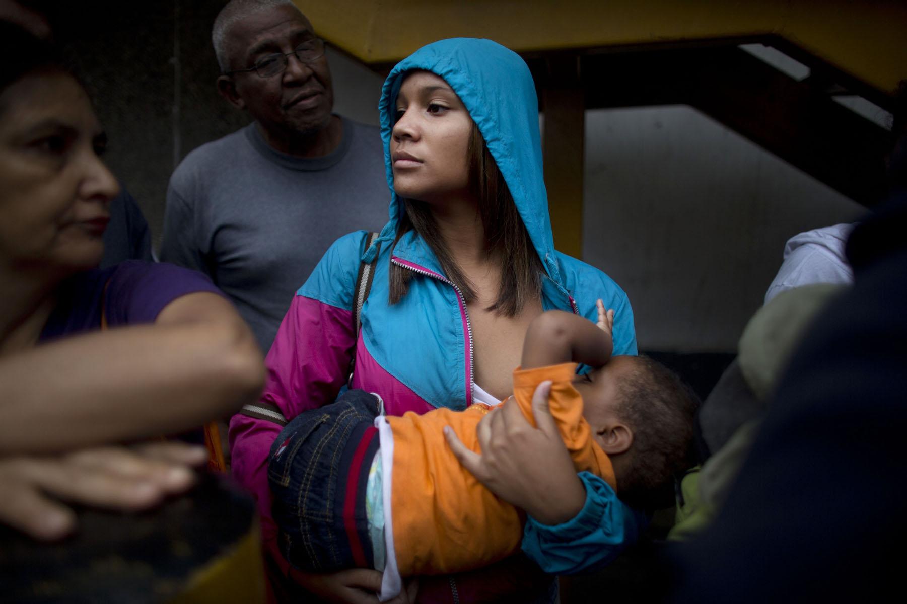 En esta fotografía del martes 3 de mayo de 2016, Madeley Vásquez, de 16 años, amamanta a su hijo de un año, Joangel, mientras espera formada afuera de un supermercado de Caracas, Venezuela, para comprar comida. Vásquez relató que una vez tuvo que correr para escapar de una riña con navajas que comenzó cuando una mujer fue acusada de meterse en la fila. (AP Foto/Ariana Cubillos)