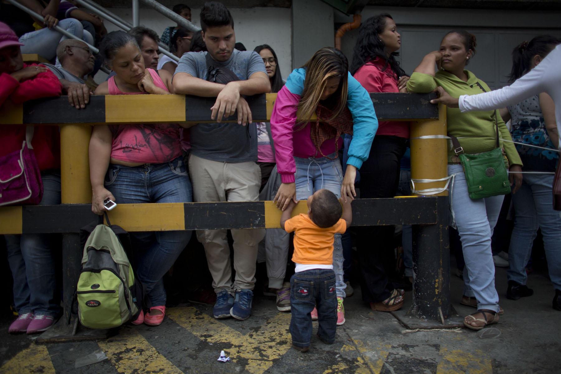 En esta fotografía del martes 3 de mayo de 2016, Madeley Vásquez, de 16 años, espera con su hijo de un año, Joangel, afuera de un supermercado de Caracas, Venezuela, para comprar comida. Joangel practicaba sus primeros pasos mientras llegaba el turno de su madre de hacer compras, que fueron dos bolsas de arroz y dos paquetes de papel sanitario. (AP Foto/Ariana Cubillos)