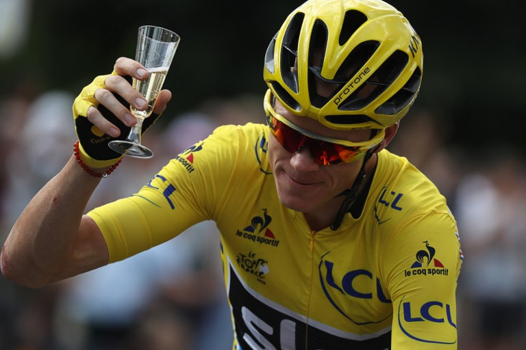 Great Britain's Christopher Froome, wearing the overall leader's yellow jersey, is handed a glass of champagne as he rides during the 113 km twenty-first and last stage of the 103rd edition of the Tour de France cycling race on July 24, 2016 between Chantilly and Paris Champs-Elysees. / AFP PHOTO / KENZO TRIBOUILLARD