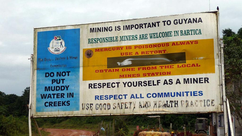Cartel de la Comisión de Geología y Minas de Guyana en la zona Itaballi-Puruni-Papishao en la carretera a la entrada al distrito minero de la Región 7