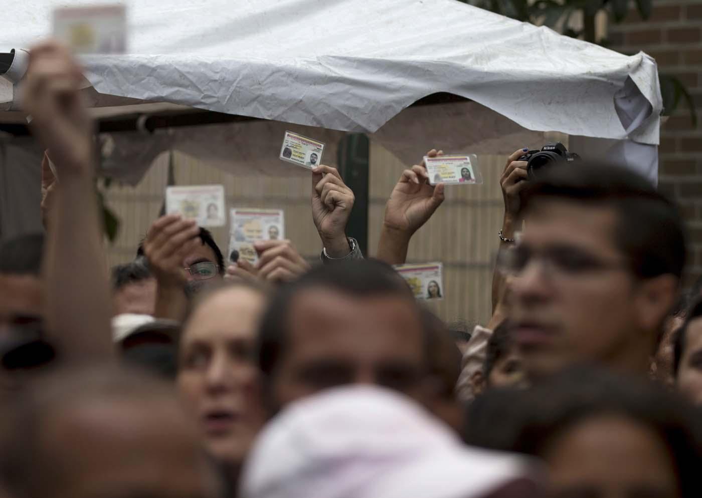 ARCHIVO - Esta foto de archivo del 24 de junio de 2016 muestra a opositores venezolanos que reclaman la validación de las firmas reunidas para un referendo revocatorio del mandato del presidente Nicolás Maduro. La coalición opositora convocó a nuevas marchas a favor del referendo el miércoles 27 de julio de 2016. (AP Foto/Fernando Llano, Archivo)