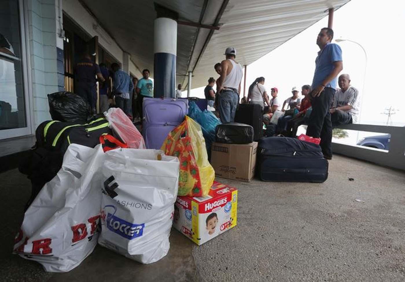 Venezolanos esperan con sus compras a un ferri privado en Trinidad para volver a casa. Foto tomada el 1 de junio del 2016. REUTERS/Andrea De Silva