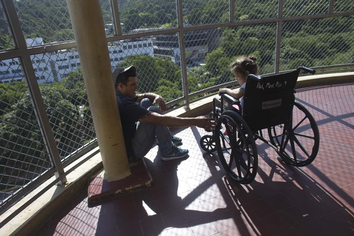 En esta imagen del 17 de agosto de 2016, Maykol Pacheco se sienta con su hija de tres años Ashley, que se recupera de una infección estafilocócica, en un balcón del Hospital Universitario de Caracas, en Venezuela. (AP Foto/Ariana Cubillos)