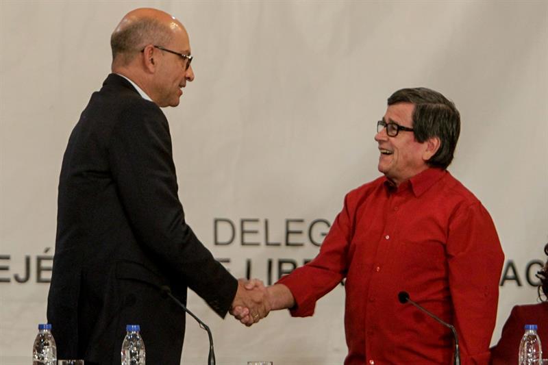 Los jefes negociadores del Gobierno colombiano Mauricio Rodríguez (i) y de la guerrilla del ELN, Pablo Beltrán estrechan sus manos en la sede de la cancillería en Caracas. EFE