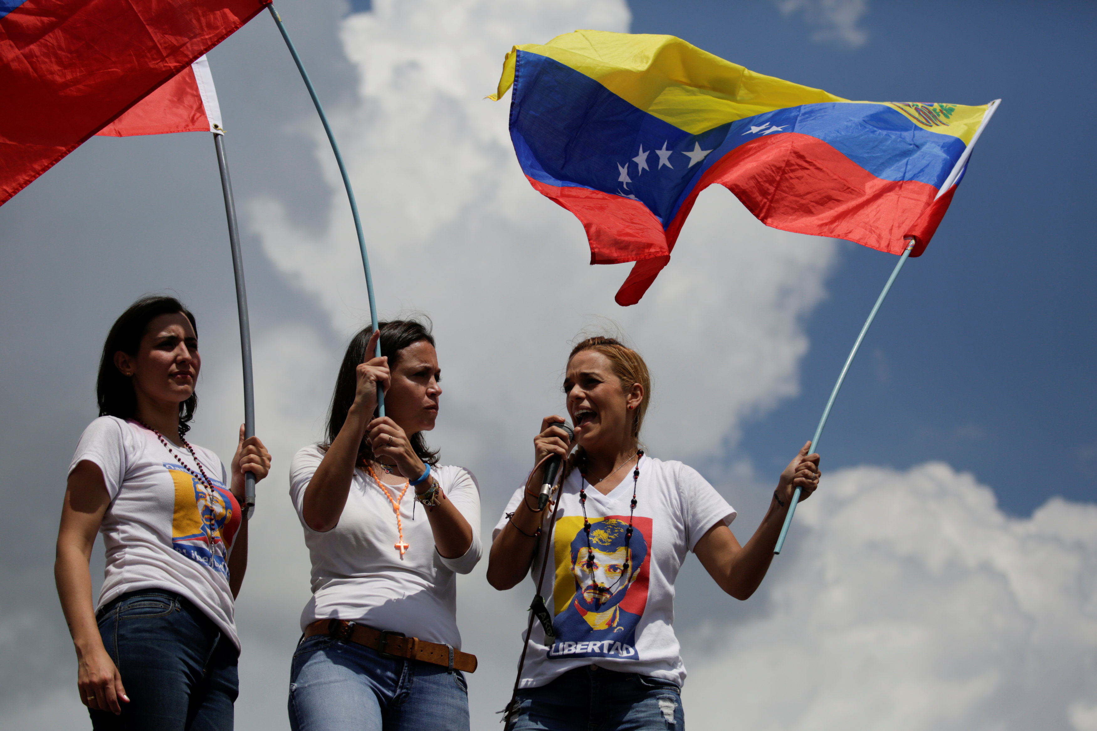 Lilian Tintori (R), wife of jailed Venezuelan opposition leader Leopoldo Lopez speaks to supporters during a rally to demand a referendum to remove Venezuela's President Nicolas Maduro, next to Venezuelan opposition leader Maria Corina Machado (C) and Patricia Ceballos, mayor of San Cristobal and wife of jailed former mayor Daniel Ceballos, in Caracas, Venezuela October 22, 2016. REUTERS/Marco Bello