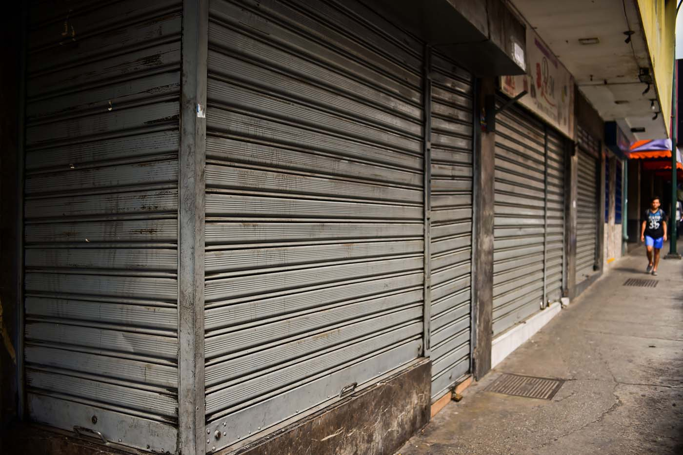 A woman walks by closed stores in Caracas, on October 28, 2016. Venezuela's opposition sought to pressure President Nicolas Maduro on Friday with a strike, which he threatened to break with army takeovers of paralyzed firms. The strike risks exacerbating the shortages of food and goods gripping the country, but it seemed to be only partially observed on Friday morning. / AFP PHOTO / RONALDO SCHEMIDT