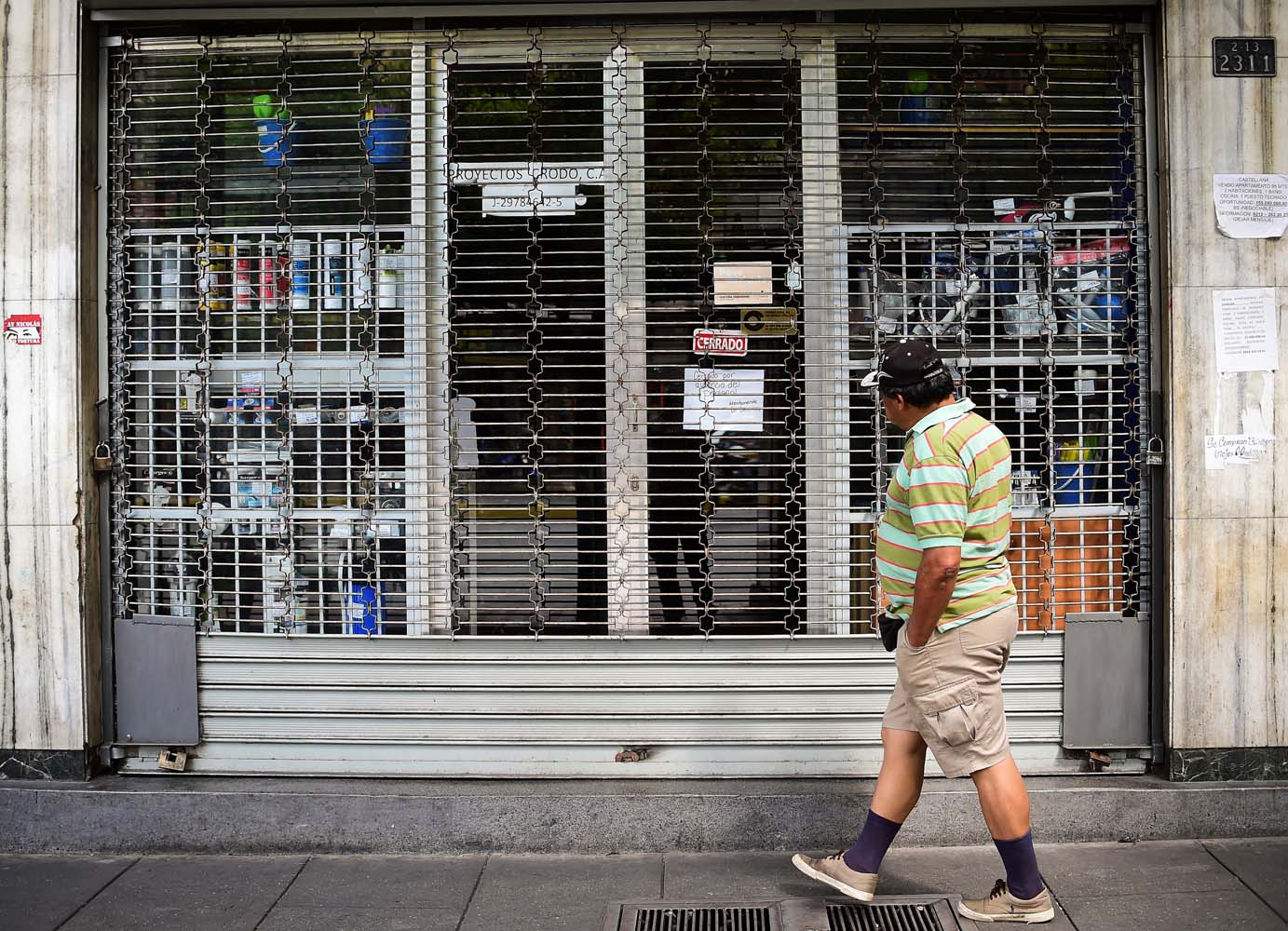 A man passes by a closed store in Caracas, on October 28, 2016. Venezuela's opposition sought to pressure President Nicolas Maduro on Friday with a strike, which he threatened to break with army takeovers of paralyzed firms. The strike risks exacerbating the shortages of food and goods gripping the country, but it seemed to be only partially observed on Friday morning. / AFP PHOTO / RONALDO SCHEMIDT