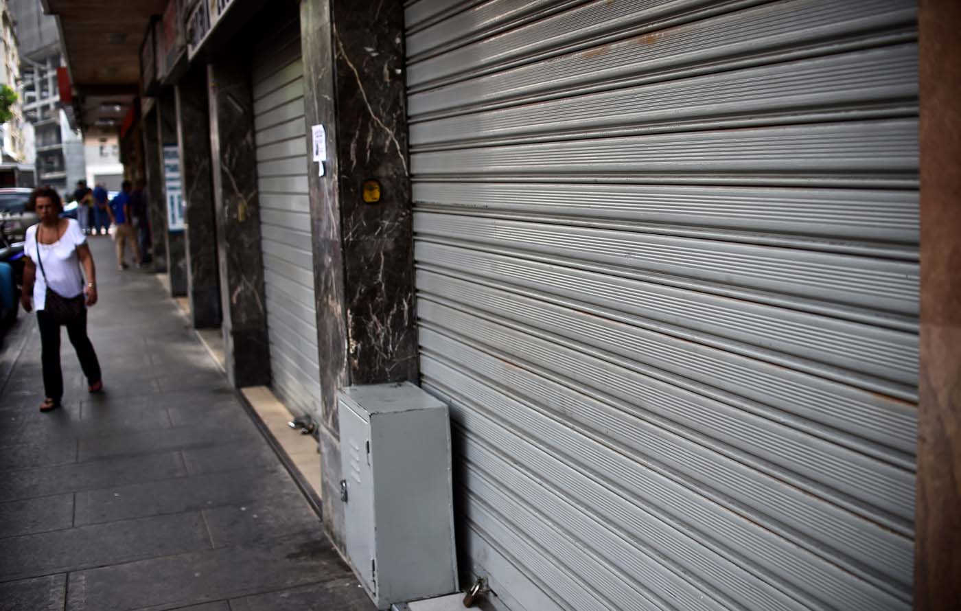 A woman walks by a closed store in Caracas, on October 28, 2016. Venezuela's opposition sought to pressure President Nicolas Maduro on Friday with a strike, which he threatened to break with army takeovers of paralyzed firms. The strike risks exacerbating the shortages of food and goods gripping the country, but it seemed to be only partially observed on Friday morning. / AFP PHOTO / RONALDO SCHEMIDT