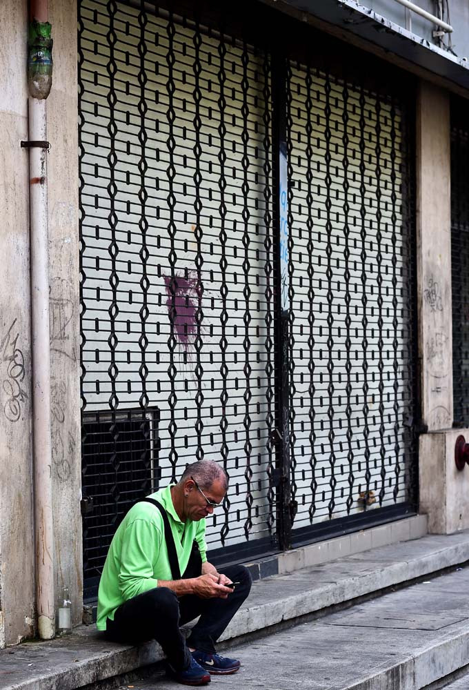 A man sits next to a closed store in Caracas, on October 28, 2016. Venezuela's opposition sought to pressure President Nicolas Maduro on Friday with a strike, which he threatened to break with army takeovers of paralyzed firms. The strike risks exacerbating the shortages of food and goods gripping the country, but it seemed to be only partially observed on Friday morning. / AFP PHOTO / RONALDO SCHEMIDT