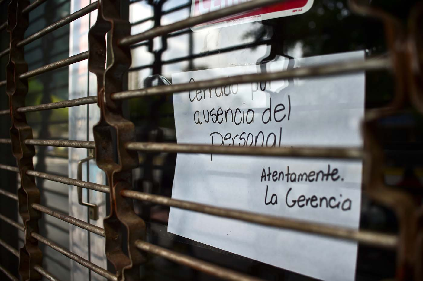"A closed store shows a sign which reads ""closed for lack of staff"" in Caracas, on October 28, 2016. Venezuela's opposition sought to pressure President Nicolas Maduro on Friday with a strike, which he threatened to break with army takeovers of paralyzed firms. The strike risks exacerbating the shortages of food and goods gripping the country, but it seemed to be only partially observed on Friday morning. / AFP PHOTO / RONALDO SCHEMIDT"