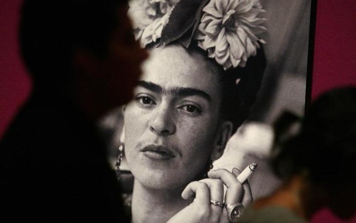 """Foto de archivo de un grupo de visitantes junto a una foto de la artista Frida Kahlo en la inauguración de la muestra """"Frida"""" en el Museo de Arte Contemporáneo de Monterrey. Ago 31, 2007. Una pintura de Frida Kahlo que nunca ha sido expuesta en público y cuyo paradero era un misterio será rematada la próxima semana en Sotheby's en Nueva York, informó el lunes la casa de subastas. REUTERS/Tomas Bravo"""