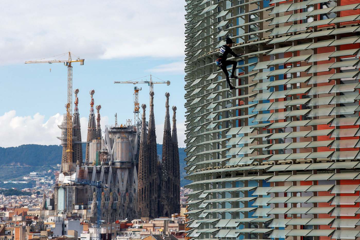 "French climber Alain Robert, also known as ""The French Spiderman"", scales the 38-story skyscraper Torre Agbar with the Sagrada Familia cathedral in the background in Barcelona, Spain, November 25, 2016. REUTERS/Albert Gea TPX IMAGES OF THE DAY"