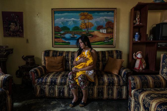 Saribeth Cordero con la ropa que usaba su hermano, William, mientras trabajaba como barbero. El bote que lo sacó de Venezuela desapareció. Credit Meridith Kohut para The New York Times