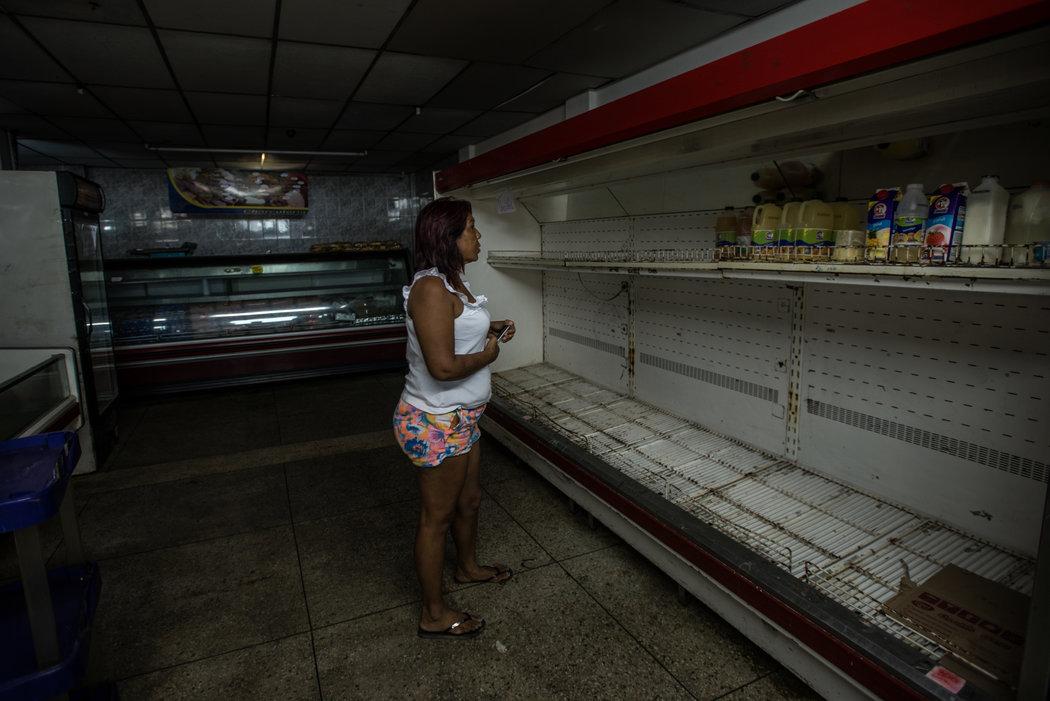 """María Piñero en un supermercado vacío de La Vela, Venezuela. """"Estoy nerviosa"""", dijo. """"Me voy sin nada. Pero tengo que hacerlo porque de lo contrario, simplemente nos moriremos de hambre"""". Credit Meridith Kohut para The New York Times"""