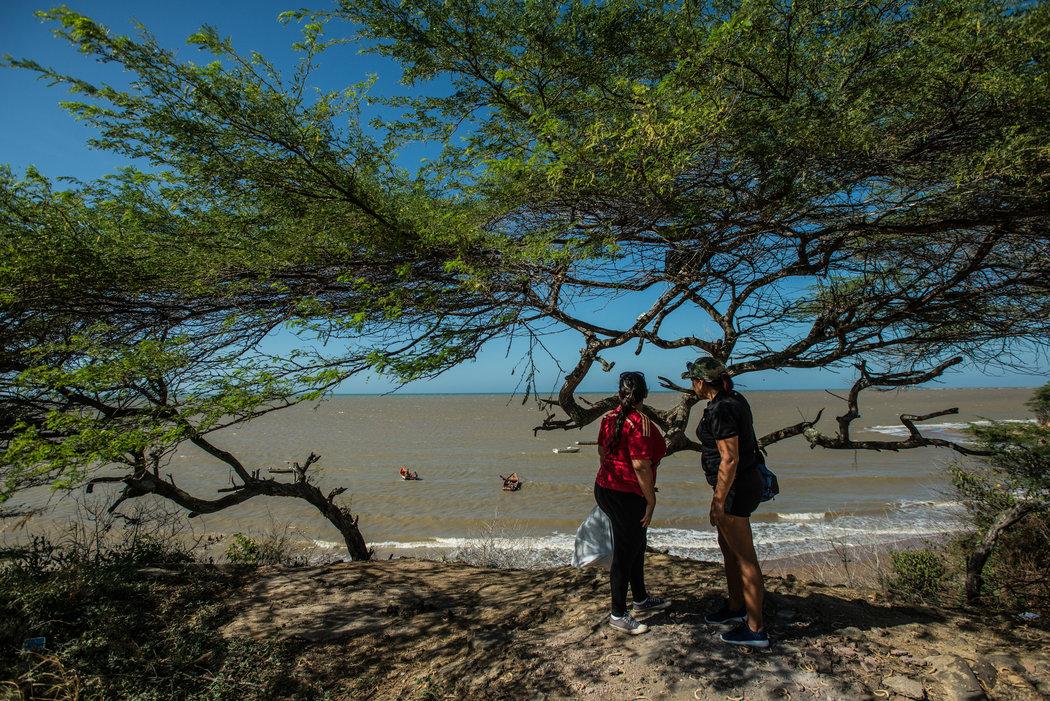 Dos inmigrantes esperan el bote que los sacará de Venezuela. Credit Meridith Kohut para The New York Times