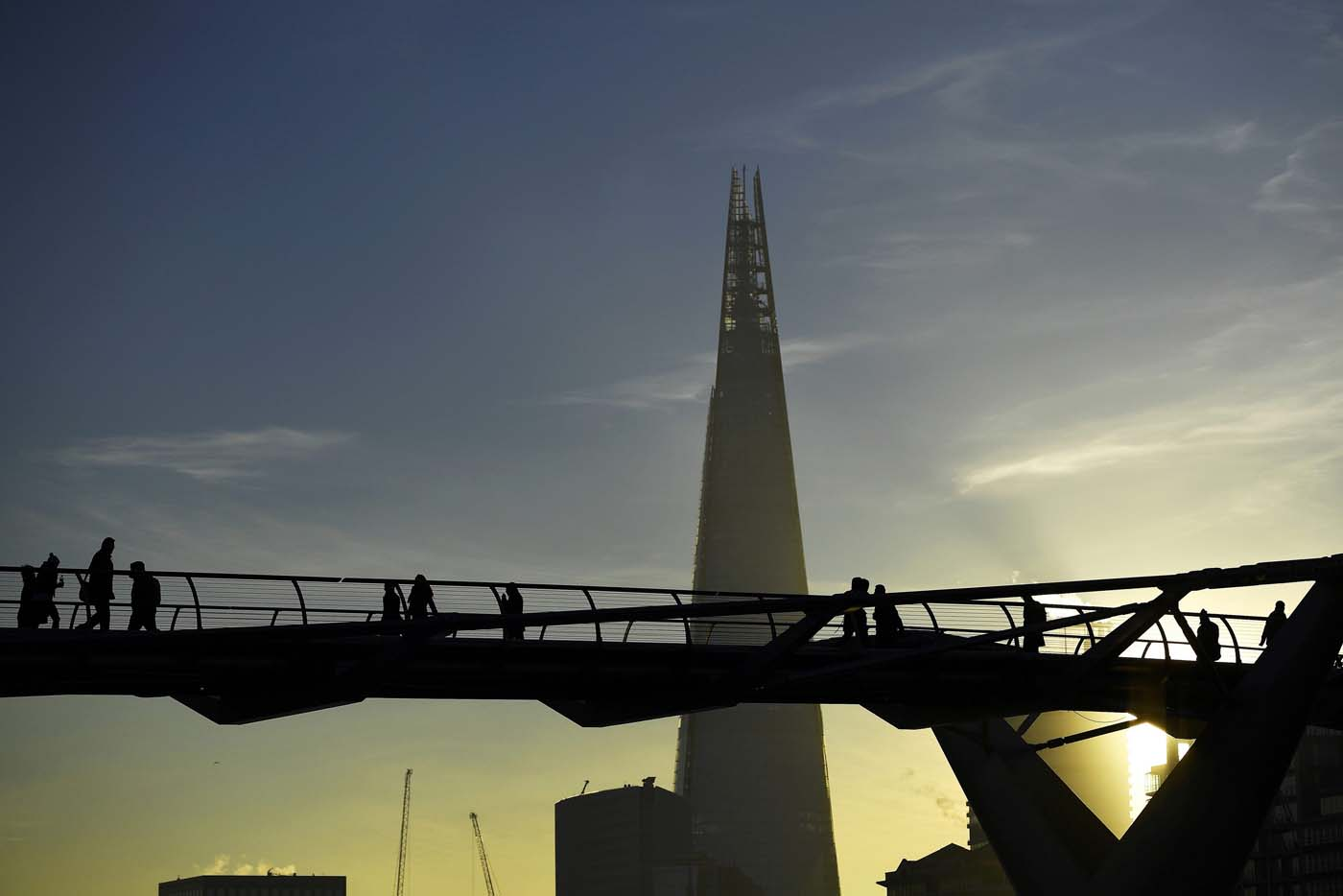 The Shard is seen as commuters make their way across the Millennium Bridge as the sun rises over London, Britain November 30, 2016. REUTERS/Dylan Martinez