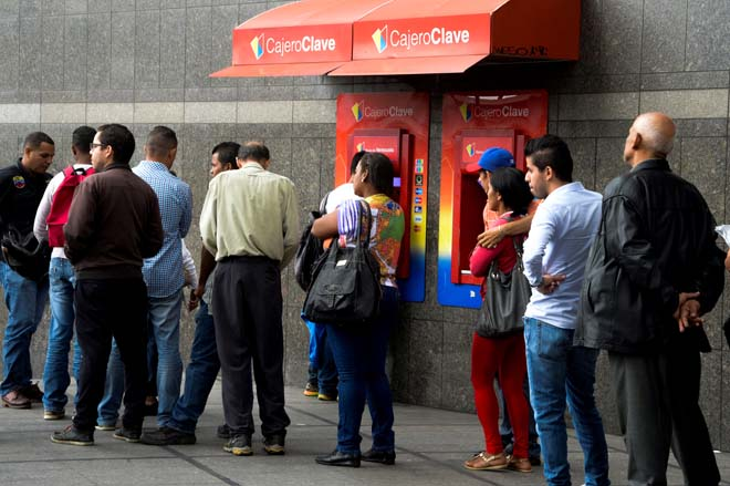 People queue to withdraw money from an automated teller machine (ATM) in Caracas on December 1, 2016. Venezuelan banks guaranteed their continued operation, after rumors about a close in December to adjust to an alleged issuance of bills of higher denomination. At the moment, the note of highest denomination is the one of 100 bolivars, that is just enough to buy a sweet. / AFP PHOTO / Federico PARRA