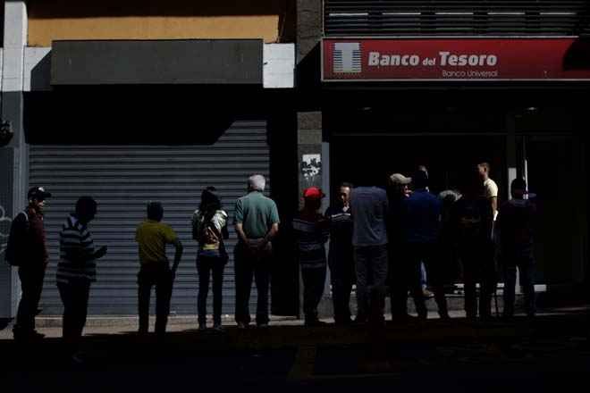 People line up to withdraw cash from a Banco del Tesoro branch in Caracas, Venezuela December 2, 2016. REUTERS/Ueslei Marcelino