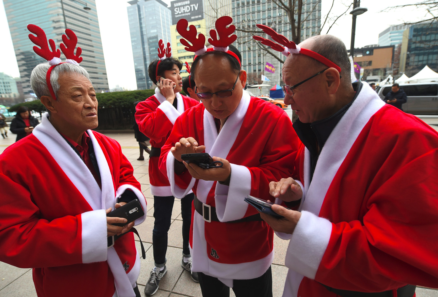 South Korean volunteers in Santa Claus outfits use their smartphones before heading out to distribute Christmas gifts at homes for prematurely born babies in Seoul on December 8, 2016. The volunteers will visit some 40 homes raising prematurely born babies in Seoul and the surrounding Gyeonggi Province. / AFP PHOTO / JUNG Yeon-Je