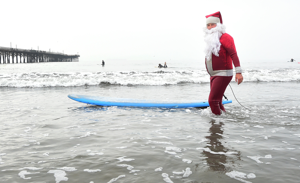 Surfing Santa, Michael Pless, makes his way out to surf at Seal Beach, California on December 10, 2016, where he runs a surfing school and has every December since in 1990's gone out to surf in his Santa Claus outfit. / AFP PHOTO / Frederic J. BROWN