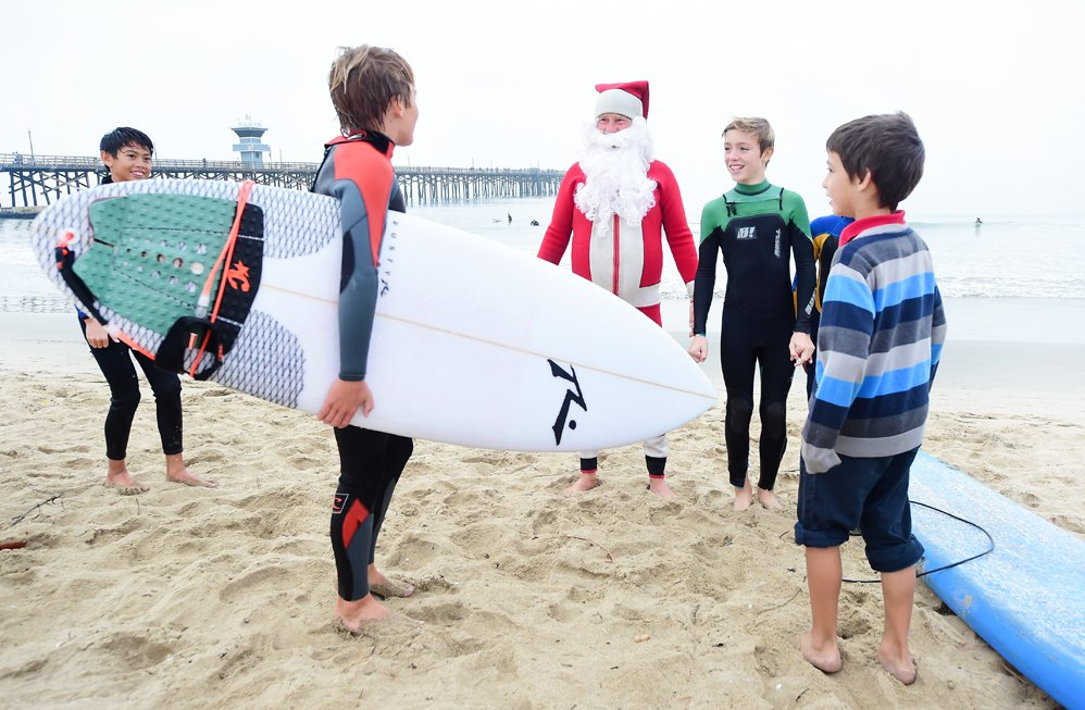 Surfing Santa, Michael Pless, meets with young surfers at Seal Beach, California on December 10, 2016, where he runs a surfing school and has every December since in 1990's gone out to surf in his Santa Claus outfit. / AFP PHOTO / Frederic J. BROWN