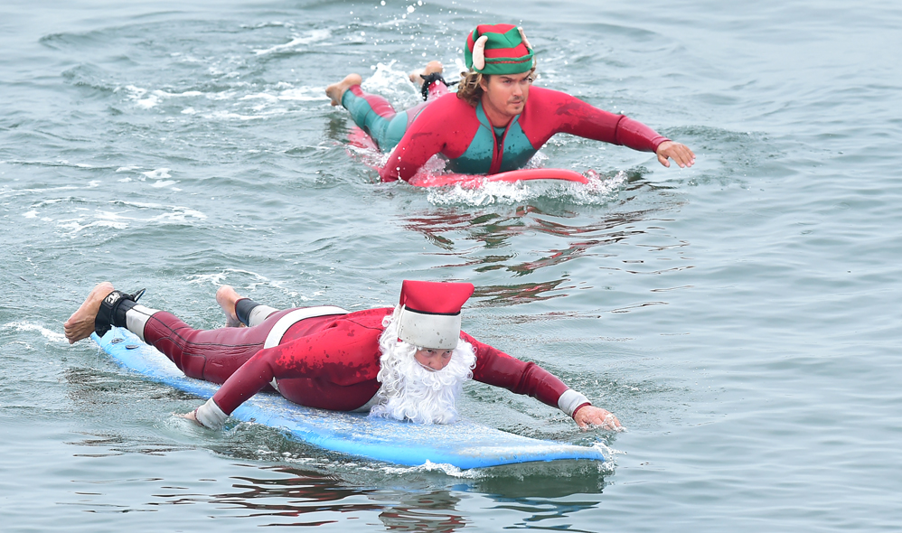 Surfing Santa, Michael Pless, and Jonathan Livingston, dressed as an Elf, make their move to catch a wave at Seal Beach, California on December 10, 2016, where he runs a surfing school and has every December since in 1990's gone out to surf in his Santa Claus outfit. / AFP PHOTO / Frederic J. BROWN