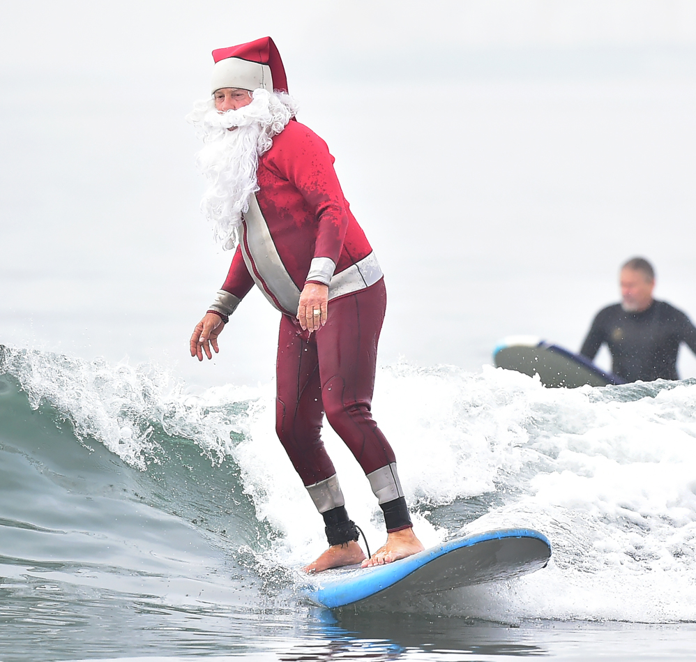 Surfing Santa, Michael Pless, surfs at Seal Beach, California on December 10, 2016, where he runs a surfing school and has every December since in 1990's gone out to surf in his Santa Claus outfit. / AFP PHOTO / Frederic J. BROWN