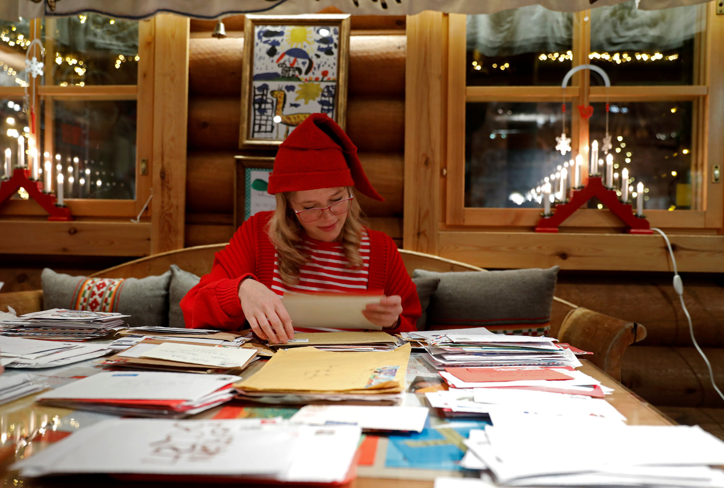 "Elina, dressed as a Christmas elf, reads letters from around the world which were sent to Santa Claus at the Santa Claus' Post Office, in the Arctic Circle near Rovaniemi, Finland December 15, 2016. REUTERS/Pawel Kopczynski SEARCH ""KOPCZYNSKI SANTA"" FOR THIS STORY. SEARCH ""THE WIDER IMAGE"" FOR ALL STORIES"